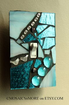 Blue Ice Mosaic Light Switch Cover Wall Plate by MOSAICSnMORE on Etsy. Single switch wall plate in Aqua/Blue Mirror glass and Blue/white/Purple swirly Stained Glass,light blue clear glass marbles, Rhine Stones and silver gems Mosaic Crafts, Mosaic Projects, Mosaic Art, Mosaic Glass, Mosaic Tiles, Stained Glass, Glass Art, Art Projects, Mirror Glass