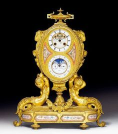 """IMPORTANT CLOCK """"AUX BELIERS"""" WITH MOONPHASE,   late Louis XVI, the movement signed THOMAS AGNEW & SONS inscribed and numbered SPECTE 27298, England, 19th century Matte and polished gilt bronze and finely painted porcelain. The oval case decorated with vase, rams' heads and flowers on 2 putti supports with garlands. The finely painted front with enamel dial and enamel ring with date, eternal calendar, astronomical signs and moon phase. Brass movement"""