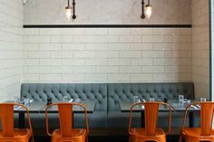 jamie's italian. orange chairs paired with steel blue booth. Beautiful