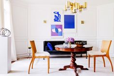 Tour a Designer's Own Luxe, Eclectic Virginia Home // White Dining Room With Blue and Purple Artwork