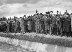 Liberated prisoners from Dachau, the German concentration camp wave in joy. Those wearing striped uniforms are political prisoners whose fate was cremation if they had not been liberated by the US 7th Army, 7th May 1945