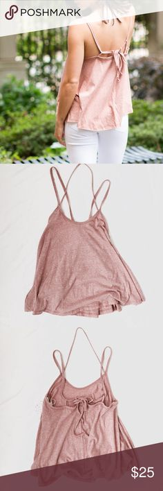 "⭐️Last One⭐️ FP Pink Strappy Tank Simple from the front, until you turn around!  This strappy tank top from Free People features a stretchy heather material in ""sunset"" pink and a flowy and drapery fit.  A cute halter strap goes around f the neck while two other straps connect to the loops in the back and end in a cute bow.  Can be untied and adjusted it needed.  Brand new with tags! Free People Tops Tank Tops"