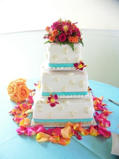 Wedding cake top with fushia orchids and orange and hot pink roses.  Loved the color combo at this beachside wedding reception!
