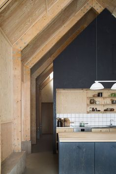 With its soaring ceiling and exposed beams and trusses, the design references barn construction. The rooms are wrapped in plywood and parts of the kitchen areset off with a graphite-colored stain from Osmo. A full-height fridge and freezer are tucked into a pantryon the other side of the sink wall.