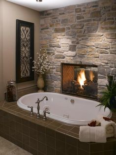 oval tub with stone wall and fireplace in guest bathroom