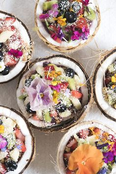 Coconut Bowls filled with edible flowers, fresh fruit, homemade granola, hemp seeds, and coconut flakes. amazebowls | designlovefest