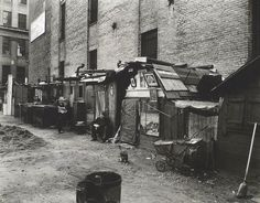 Huts and unemployed, West Houston and Mercer St., Manhattan.    Notes: Men sit in front of huts made of salvaged materials, some decorated with pictures, cat plays in front near baby carriage. Code: III.G.    Source: Changing New York / Berenice Abbott. (more info)    Repository: The New York Public Library. Photography Collection, Miriam and Ira D. Wallach Division of Art, Prints and Photographs.
