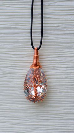 "Tree of Life wire wrapped around Crystal pendant on black cord necklace. Pendant is 1"" in length. Recycled Beautifully is proud to say that ""We Recycle""! All of our hand wrapped jewelry is made using recycled copper or aluminum wire that we pull out of T.V.'s that people throw in the trash. By using recycled wire we are able to not only keep these items out of the landfills but we are also able to keep our jewelry priced at amazingly low prices."
