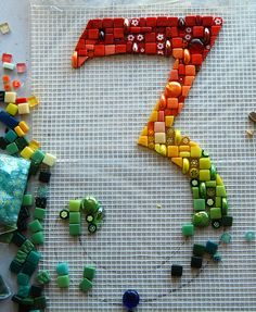 The start of a big project...for myself. Repainting the house and garden walls, and the 'pillars' around the door were in such a bad state decided to mosaic them instead ,in a 'gaudi-esque' sort of way, with white tiles. Mike came up with the suggestion of a big house number. Its going to be 34, slightly offset. Ha ,wasnt going to do a rainbow mosaic for a while, but when i got started it just sorta....grew!!! Not done anything on mesh before , any tips on applying it to the outside wall…