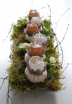 Egg candle Easter or spring decor: make hand knitted cords, wrap these around small card board rolls to make candle holders. Decorate with feathers. Make egg candles by melting candle left-overs into empty egg shells and adding a wick. Put the egg candles and their holders on a tray with moss, birch twigs and Primroses or other spring flowers. From mamas kram, 12 maart 2013.