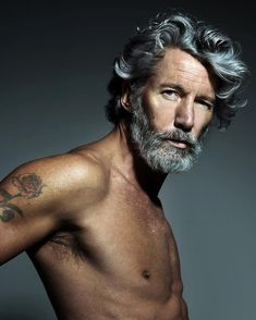 Man - older Rough skin, deep contours - no blush. Thick facial hair, dark eyes, creased brow.