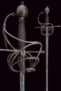 """A rapier with Caino mark. Dating: circa 1600. Italy Straight, double-edged blade, grooved at the base with unclear inscriptions, concave ricasso with the signature """"CAINO"""" and a slightly visible mark; iron hilt with straight quillons, guard and three parry rings with central knots, large oval pommel. Wooden grip with iron wire binding and moor's heads (probably later). In patina. To be cleaned. Length 137.5 cm."""