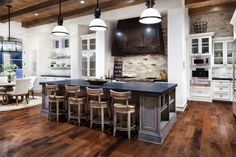 white kitchen, marble counter top, brick walls, exposed beams, dark wide plank floors.