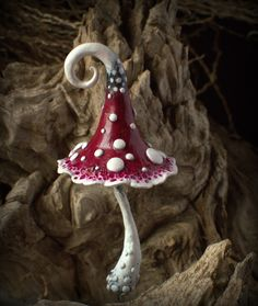Red white black fantasy mushroom for fairy gardens,pot decor, interior or exterior inhabitant.Elves,gnomes,fairies and of course trolls are his\hers soulmates. Made from polymer clay and hand painted with acrylic paints,sealed with three layers of varnish.Embedded with aluminium wire to place in flower pot or somewhere else to give a bit of magic. Indoor and outdoor use, should be taken inside for winter.The gloss dont like frozen temperatures.    Its about 11,5 cm tall and 5 cm wide.  Take…