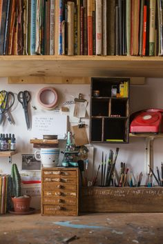 """On the shelf below, art supplies intermingle with various decorations and props that I've collected over the years."" #homeoffice"