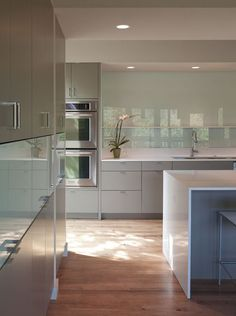 noninvasive lighting, a flat-planel door style on  cabinets, the full-height glass backsplash