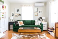 Dark green velvet sofa, cowhide rug, white Ikea shelves, small white table lamps, sheer curtains, gold curtain rod, mid-century coffee table