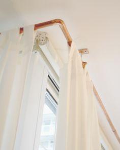 ikea curtains, DIY copper rods, hidden roller shade. whoa.