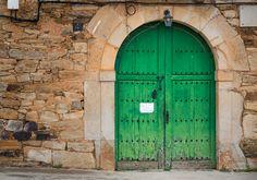 Linda porta verde em arco, numa  parede e portal de pedras em Murias de Rechivaldo, município de Astorga, Comunidade Autônoma de Castela e Leão, Espanha.  Fotografia: Christian Twehues.