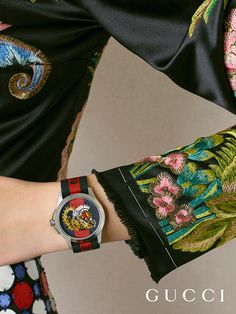 A tiger is embroidered onto the Gucci Le Marche Des Merveilles 38mm watch featuring a green and red Web nylon strap.