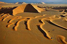 """RUB AL KHALI • ARABIA SAUDITA  Dune di recente formazione nel deserto saudita il cui nome vuol dire """"regione vuota"""". In alto, una duna a stella che, data la mole, non si muoverà per decenni."""
