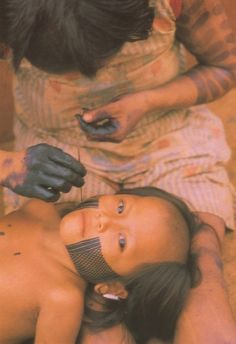A Kayapó Indian mother paints her son's face with a dye called Genipap. The Amazon Rainforest-Database.com