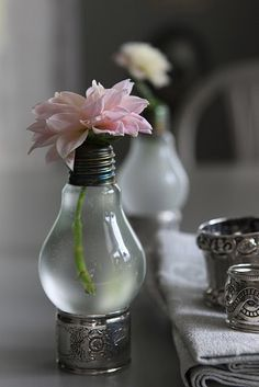 Easy and Unique DIY Vases: Cut the bottom of a used light bulb off and empty the bulb of its contents. Rinse it out with water (and maybe some soap) to clean out the metal. Next, fill it with water and then set it on something that will hope it upright, such as a napkin ring.