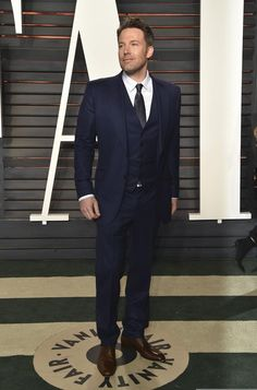 Ben Affleck star of Batman v Superman: Dawn of Justice, seen in Gucci Made to Measure midnight blue two-button three-piece Marseille suit to the 2016 Vanity Fair Oscars party.