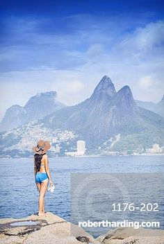 A 20-25 year old young Brazilian woman standing on the Arpoador rocks with…