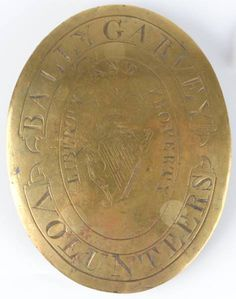 """c. 1780-90: BALLYGARVEY VOLUNTEERS OFFICER'S SHOULDER BELT PLATE  An extremely good officer's shoulder belt pate. Engraved with the crowned Maid of Erin harp surrounded by the words Liberty and Property"""" and scrolls above and below containing the name of the regiment.   Scarce."""