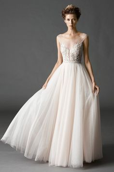 Dreamy, ballerina inspired A-Line gown, featuring an Illusion yoke with a plunging neckline, delicate beading and Swarovski Crystals on the bodice. Pearl buttons down the back with a full, Soft Net skirt. | Watters | Style: KALIAH