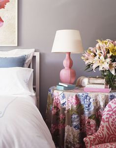 In a corner of the bedroom, a round table with an elegant table skirt of Manuel Canovas's Bragance fabric in taupe. Double-gourd pink lamp by Christopher Spitzmiller, available through Hollyhock.