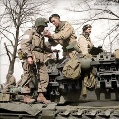 A paratrooper from the American 17th Airborne Division gets a light from a Churchill tank crewman of 6th Guards Armoured Brigade near Dorsten in North Rhine-Westphalia, Germany. 29th March 1945