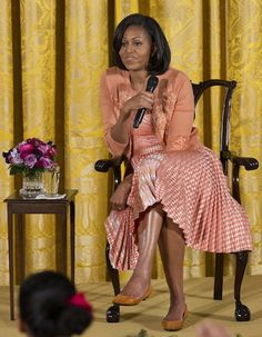 Mrs. O hosted an event for children at the White House.  She's wearing a gingham pleated skirt with a L'Wren Scott embroidered peach cardigan.