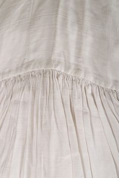Detail sleeve, shirt, 18th century. White linen of voluminous cut, with two buttonholes to collar and flounce to neck opening.
