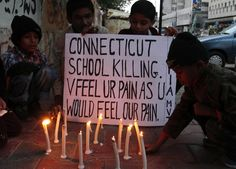 Pakistani children light candles to pay tribute to Sandy Hook Elementary School shooting victims in southern Pakistani port city of Karachi on Dec. 15, 2012