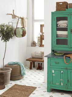 Natural decorated cottage entrance with indoor olive tree, baskets, wooden bench, green vintage linen cupboard, old tile floors, branch hanger.