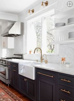 white and black kitchen with gold drawer pulls and marble