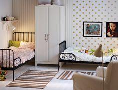 Tyttöjen huone, jossa kaksi jatkettavaa sänkyä, vaatekaappi ja lepotuoli