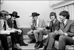 The Beatles hanging out while their manager Brian Epstein handles a phone call.