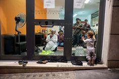 La preghiera prima del Iftar , la cena per rompere il digiuno nel mese del Ramadan , dentro un negozio di immigrati del Bangladesh,un bambino italiano guarda incuriosito gli uomini che pregano.