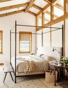 Bright, spacious, and lofty bedroom with neutral colors, exposed ceiling beams, canopy bed, and small flower arrangement