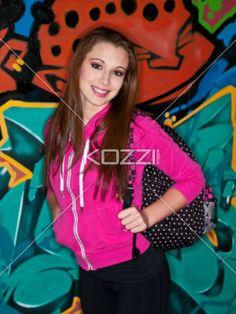 portrait image of a student aganist graffiti. - Portrait image of a teenage student with school bag aganist graffiti. Model: Brittany Beaudoin
