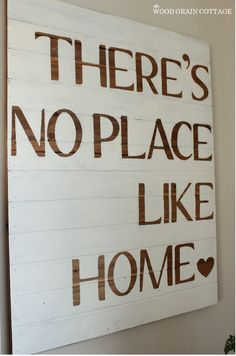 DIY Sign | The Wood Grain Cottage. Letters were cut out and placed then traced and then she hand painted around them letting the wood show through.