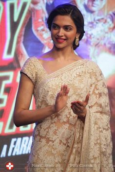 Deepika Padukone in a white lace saree or sari and blouse and statement earrings. Love the red lip  and hairstyle.