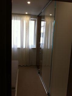 Jednokrídlové posuvné dvere s tlmeným dovieraním z kaleného bezpečnostného skla.