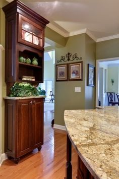 love this granite countertop paired with the cherry wood and green wall color!