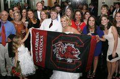 """""""My husband and I are both USC alumni. At our wedding we had all our fellow Gamecocks out on the dancefloor to dance to Sandstorm, but not before we took a quick pose with the flag.  We got married during the LSU away game last year, but don't worry we had the game playing in the bar on a big screen TV (despite the parents disapproval)."""" Have a great Gamecock wedding photo or other fan shot? Email it to us at gamecockathletics@gmail.com!"""