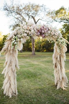 """We were trying to keep it bohemian and natural but greenery doesn't really pop in an outdoor ceremony in a green field with green trees in the background,"" planner and designer Julie Savage Parekh of Strawberry Milk Events says of the ceremony arch. So pampas grass covered the structure, which was topped with groupings of flowers."