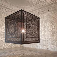 Moucharabié par Anila Quayyum Agha coupé au laser dans du bois. Il transforme la pièce grâce au principe d'ombres chinoise.